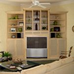 Built in corner TV cabinet idea with upper shelves and under cabinets a white ceiling fan light cream sofa a glass top table grey wool area rug for entertainment center