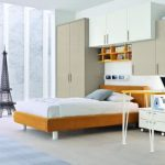 Cabinet system integrated with closet storage and bookcases a simple work desk with chair loft wood bed with white bedding light blue bedroom rug cool kids' chair a miniature of Eifel