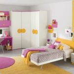 Corner L shape closet storage design sweet pink desk with pink and orange drawers and bookshelves bold pink chair white bed with orange headboard white bedside table round purple rug larger yellow rug