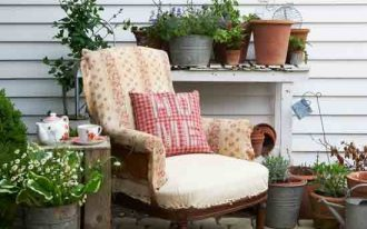 Country garden idea with an arm chair with pillow rustic side table mini garden in pots
