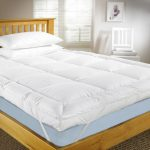 Cozy IKEA mattress topper with white pillows wooden bed frame idea with wooden headboard