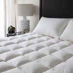 Cozy mattress pad IKEA for king bed with pillows and black headboard