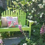 Cozy outdoor wooden chair with throw pillows in home mini garden designed by Country Garden Magazine