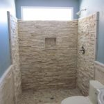 Doorless shower idea with beautiful natural stone wall system a wall niche for putting some bathing supplies wall mounted showerhead fixture a modern toilet in white