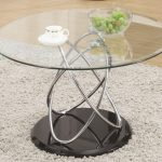 Frameless round glass and metal coffee table with stainless steel legs and glossy black base white shag rug