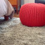 Grey shag rug designed by IKEA a bright red decorative chair