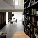 Huge home library with wooden stairs beside it a larger table for six chairs