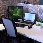 L Shape Office Desk Design In White A Laptop A Computer Screen A Office Chair A Table Lamp