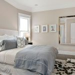 Light grey wall paint white ceiling paint white bedding bed furniture with higher white headboard grey bedcover black bedside tables white table lamps cowhide rug mirror with silver frame