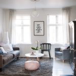 Medium size IKEA shag rug in grey color a cozy sofa with decorative pillows a white round coffee table a pink seed chair a black wooden chair a corner armchair with pillows