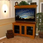 Modern corner TV cabinet idea made of wood a corner decorative plant with pot two wood boxes storage in different size