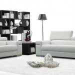 Modern white sofas with headrest white area rug large black shelving unit for books and decorative pieces a standing lamp a black side table in modern style