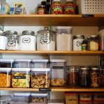 Organizing kitchen supplies in wooden shelves unit