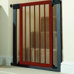 Red stain light metal safety gate idea for kids that is installed in stairwell