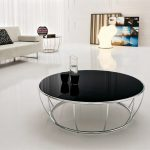 Round black glass top table with steel legs for minimalist living room a white sofa with black pillow a round side table with metal legs