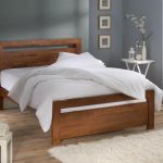 Semi rustic wood bed frame with simple headboard white bed linen white bedcover and white pillows white wool bedroom rug white side table