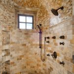 Shower space in unique concept with natural stone wall system and ceiling heldhand showerhead fixture wall mount showerhead fixture