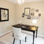 Simple classic office desk in black an office chair in dominant white white area rug a cluster of frames in various sizes a pendant chandelier a mirror with black frame