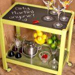 Simple cocktail cart made of lightweight metal several beautiful cocktail glasses a metal ice container two glass fruits containers