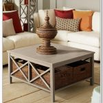 Simple coffee table with under boxes storage white modern sofas with orange red and brown pillows wood planks floors