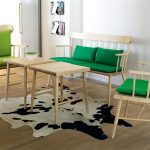 Simple wood chairs with deep green and ligher green cushions a simple wood table cowhide area rug wood planks floor idea