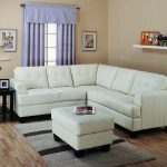 Slim sectional sofa in white for living room a white ottoman furniture small wool area rug black stained wood side table a table lamp floating white shelf blue window curtain with upper shade
