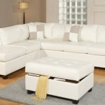 Slim white sectional with single chaise and white light brown throw pillows white ottoman with linen storage underneath small light grey wool rug wood floors