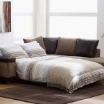 Sofa bed furniture with strips pattern neutral colored pillows and brighter neutral bed linen a black area rug wood floors wooden side table with picture frames and table lamp a corner decorative plant