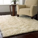 Soft white shag rug IKEA in medium size an arm chair a wooden side table glossy dark stained wood floors