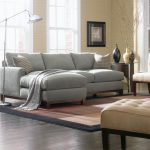Three piece sectionals with a chaise in light grey a metal modern standing table an area rug in brown color a side table with decorative vases dark stained wood plank floor idea