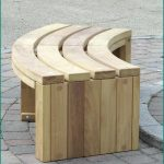 Unfinished wood bench in curve shape for outdoor use
