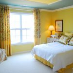 Warm yellow wall system white bed linen yellow bedding yellow pillows light cream corner chair white drawer system as bedside tables large white bedroom rug yellow curtains with metal rods