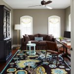 Wendt Design Group interior decorator Houston for beaitiful modern home office room with modern brown sofa black filing cabinets blue yellow black flower rug classic wooden table and chair
