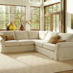 White L shape with brown throw pillows textured white area rug glass windows with wood trims