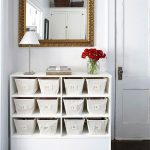 White open shelves with white box storage a modern white table a pile of books a beautiful glass pot with red roses a decorative mirror with gold tone frame
