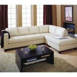 White stationary sectional sofa black stained wood coffee table with shelf underneath shag rug in light brown color