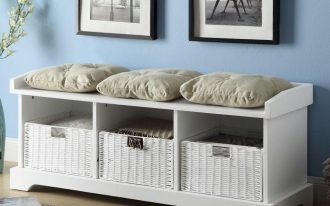 a white wooden bench design with white rattan storage boxes underneath and three throw pillows