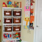adorable and unique way displaying kids art idea with metal hanger on creamy wall aside storage