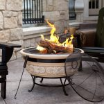 adorable classic white chiminea fire pit idea with vault cover and metal legs and carved bosy and stone wall and concrete patio and wooden chairs