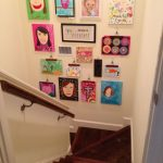 adorable idea of displaying kids art idea on the wall before stairs with picture and small painting and wooden stairs