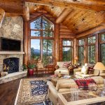 adorable log cabin style home design with log wall and log ceiling and hardwood floor and rustic stone fireplace and cream seating and patterned area rug and glass window