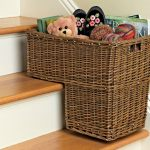 adorable natural basket idea for stairs made of rattan with fitting shape with toys on beige colored steps aside white wall
