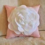 adorable small square ligh pink pillow design with white flower accent on the surface on furry sofa