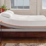 adorable tempurpedic adjustable base design in white color with orange line and wooden platform and wooden floor and table lamp and metal table and brick wall and area rug