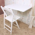 adorable white fold down laundry table beneath patterned white wallpaper with white chair on brown furry rug