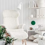 Adorable White Scandinavian Living Space Idea With Vertical Stripe Patterned Wall And Wall Bookshelves And White Area Rug And Potted Plants And Cozy White Reading Chair