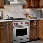 adorable wooden brown avanti compact kitchen design with white patterned backsplash and cooktop and white top