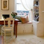 beige shabby cic bookshelves with banquette and wooden desk and white chair and glass window and wooden floor