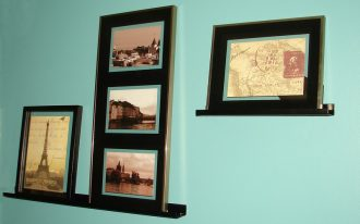 black metal picture ledge shelf or shelves with four photo frames installed on blue paint wall