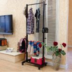 black portable ikea clothes drying rack with storage in mud room aside tv console and red rose flower vas
